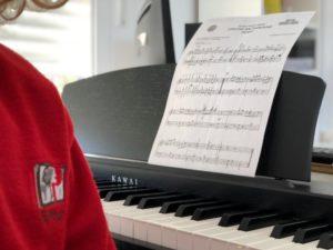 Alumno con partitura al piano en la escuela de música del Colegio el Pinar en Málaga