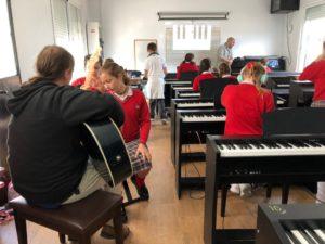 Alumnos tocando las guitarras y pianos en grupo en la escuela de música del Colegio el Pinar en Málaga